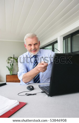 Portrait of a senior man with a laptop computer - stock photo