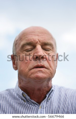 Portrait of a senior man with eyes closed - stock photo