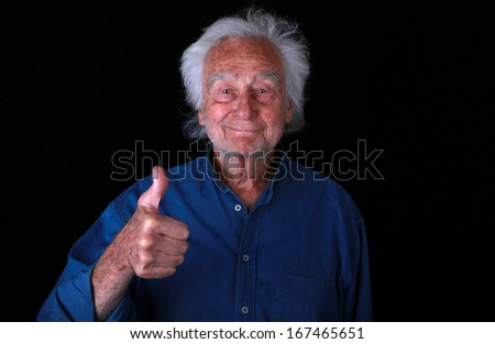 Portrait of a Senior Man with Thumbs Up for Support on Black Background - stock photo