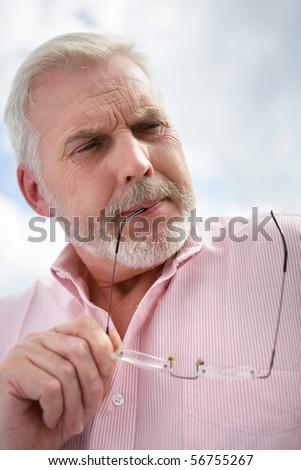 Portrait of a senior pensive holding eyeglasses - stock photo
