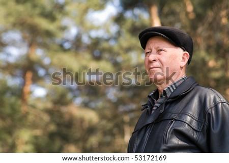 portrait of a senior person reposing in park - stock photo