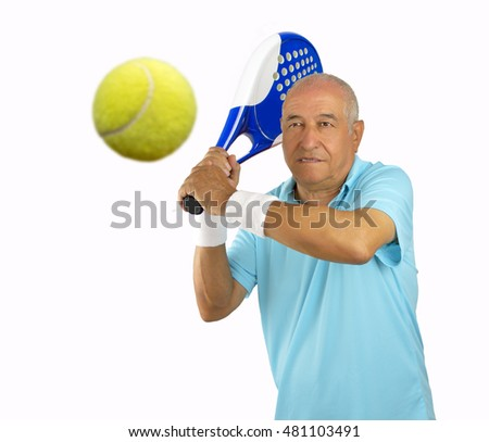 portrait of a senior sportman playing paddle tennis standing and swatting the ball
