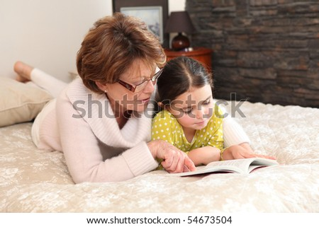 Portrait of a senior woman and a little girl stretched out on a bed reading a book - stock photo