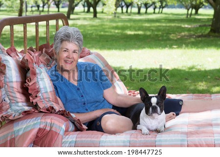 Portrait of a senior woman and her Boston terrier on an old, quilt-covered bed placed in walnut grove as her summer retreat. - stock photo