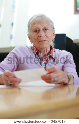 Portrait of a senior woman at home sitting at the table with papers. Shallow DOF. - stock photo