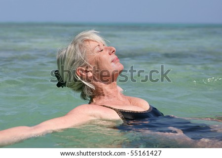 Portrait of a senior woman bathing in the sea - stock photo