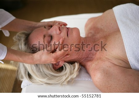 Portrait of a senior woman being massaged - stock photo