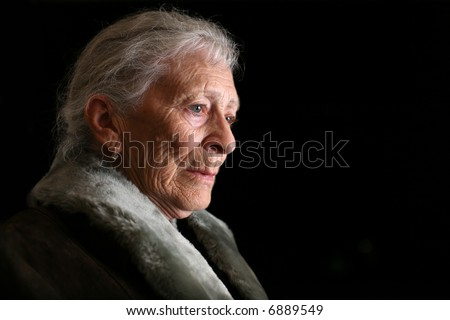 Portrait of a senior woman contemplating. Isolated on black background. - stock photo