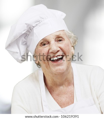 portrait of a senior woman cook smiling, indoor - stock photo
