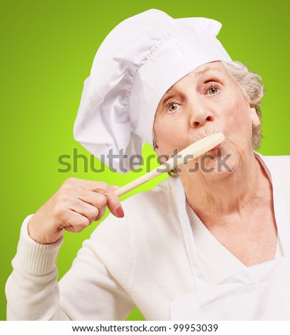 portrait of a senior woman cook with a wooden spoon on her mouth over a green background - stock photo