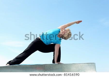 Portrait of a senior woman doing yoga outdoors - stock photo