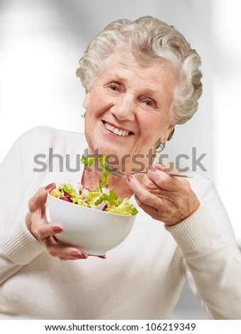 portrait of a senior woman eating a fresh salad indoor