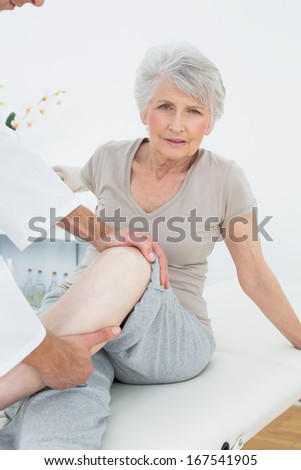 Portrait of a senior woman getting her leg examined at the medical office - stock photo