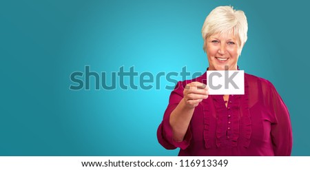 Portrait Of A Senior Woman Holding A Blank Card On Black Background - stock photo
