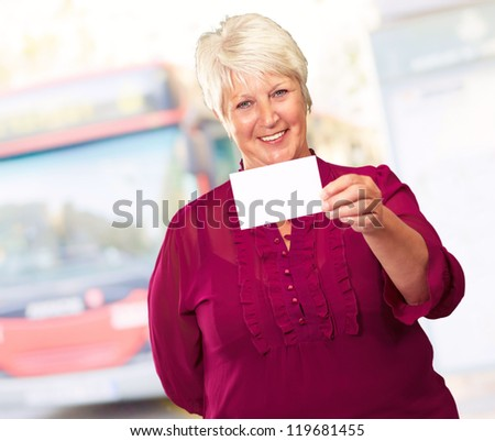 Portrait Of A Senior Woman Holding A Blank Card, Outdoor - stock photo
