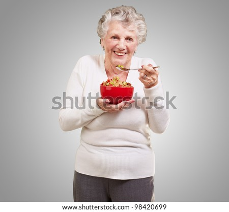 portrait of a senior woman holding a cereal bowl against a grey background - stock photo