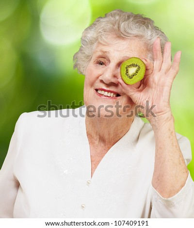portrait of a senior woman holding a kiwi in front of her eye against a nature background - stock photo