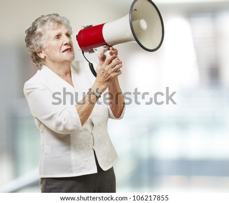 portrait of a senior woman holding a megaphone against an abstract background - stock photo
