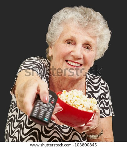 portrait of a senior woman holding a pop corn bowl and changing channel of the tv over a black background