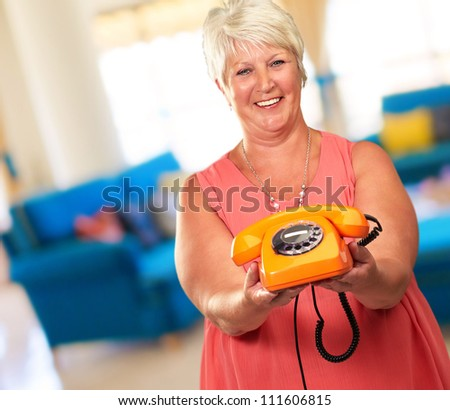 Portrait Of A Senior Woman Holding A Retro Phone, Indoor - stock photo