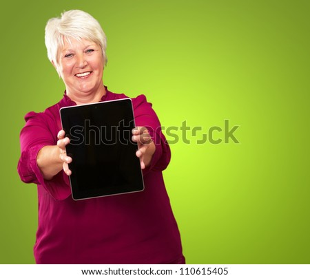 Portrait Of A Senior Woman Holding A tablet On Green Background - stock photo
