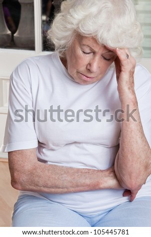 Portrait of a senior woman holding her head in pain . - stock photo