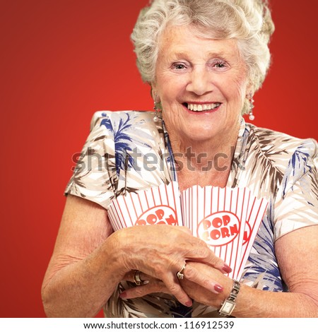 Portrait Of A Senior Woman Holding Popcorn Box On Red Background - stock photo