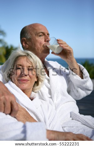 Portrait of a senior woman in bathrobe and a senior man in bathrobe drinking a glass of milk - stock photo