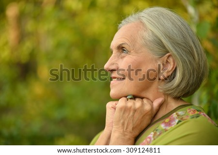 Portrait of a senior woman in summer park - stock photo