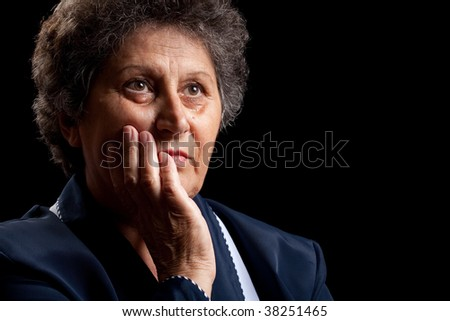 Portrait of a senior woman isolated on black - stock photo