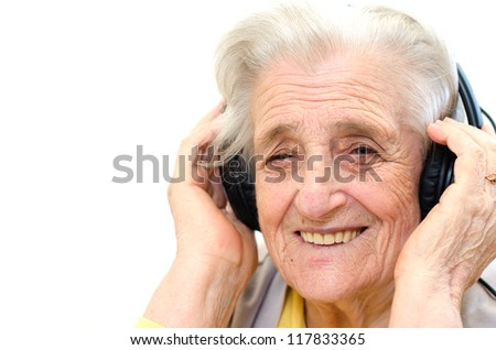 portrait of a senior woman listening to music on white background - stock photo