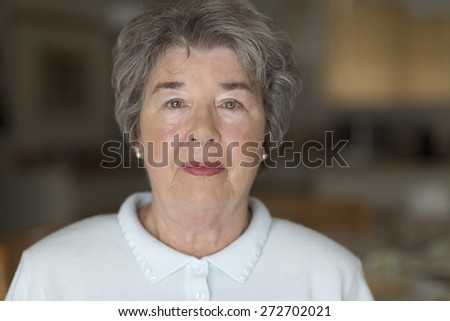 Portrait Of A Senior Woman Looking At The Camera - stock photo