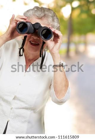 Portrait of a senior woman looking through binoculars, outdoor - stock photo