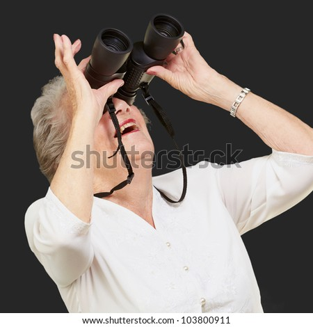 portrait of a senior woman looking through binoculars over a black background - stock photo