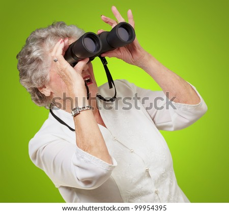 portrait of a senior woman looking through binoculars over a green background - stock photo