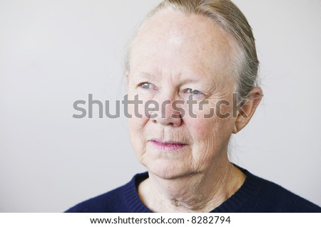 Portrait of a senior woman looking towards a light source. - stock photo