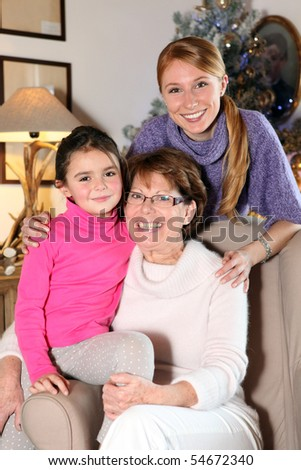 Portrait of a senior woman on an armchair next to a woman and a little girl