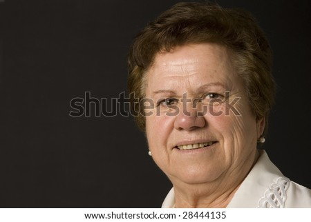 Portrait of a senior woman on dark background - stock photo