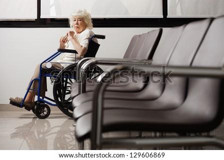 Portrait of a senior woman on wheelchair in hospital lobby - stock photo