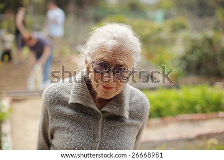 Portrait of a senior woman outdoors, looking in camera. Shallow DOF. - stock photo