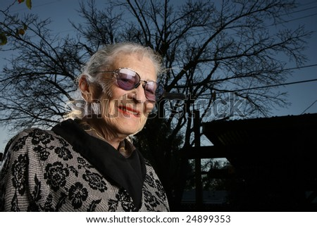 Portrait of a senior woman outdoors, smiling - stock photo