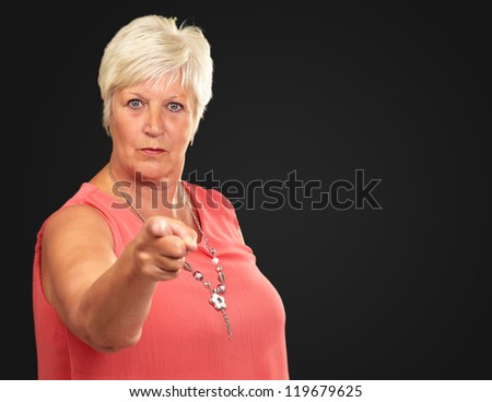 Portrait Of A Senior Woman Pointing Finger On Black Background - stock photo