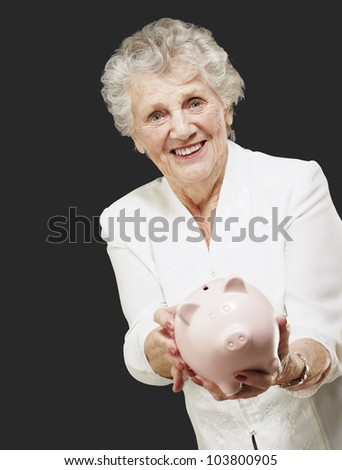 portrait of a senior woman showing a piggy bank over a black background - stock photo