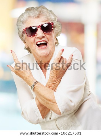 portrait of a senior woman smiling and wearing sunglasses against an abstract background - stock photo