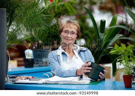 Portrait of a senior woman standing at check out counter in garden center - stock photo