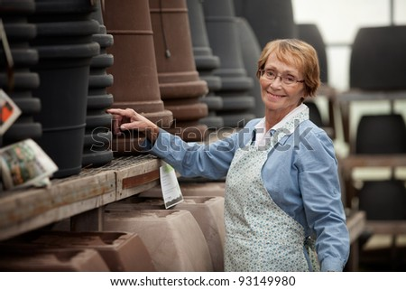 Portrait of a senior woman standing by pots in garden center - stock photo