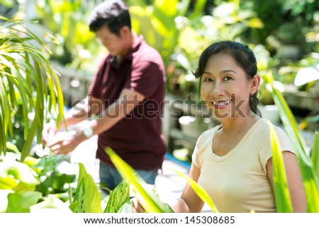 Portrait of a senior woman standing in the garden on the foreground - stock photo