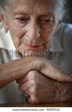 Portrait of a senior woman thinking with head on nands. Shallow DOF. - stock photo