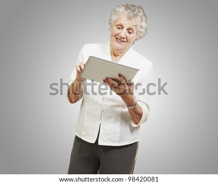 portrait of a senior woman touching a digital tablet over a grey background - stock photo