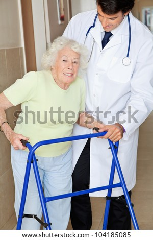 Portrait of a senior woman using walker standing by young doctor